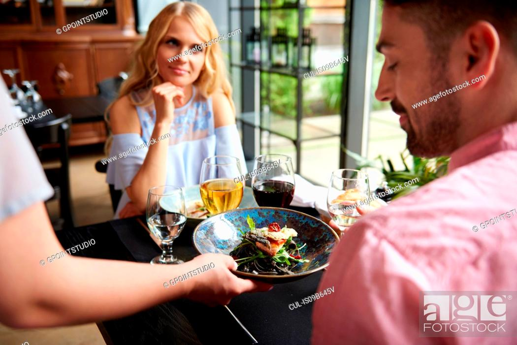 Stock Photo: Over shoulder view of waitress serving lunch to couple at restaurant table.