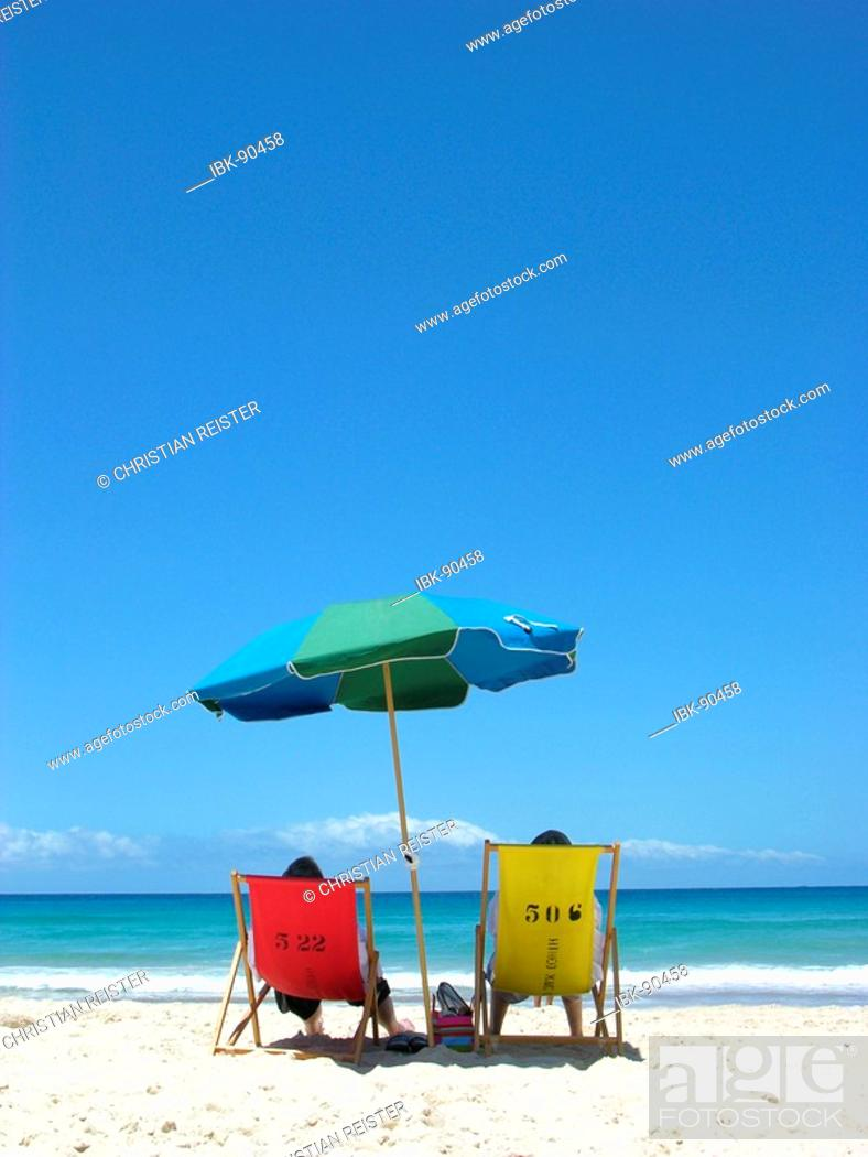 Stock Photo: A man and a woman sit on a red and a yellow canvas chair, in the center a sun screen, at the otherwise deserted beach at the Bondi Beach, Sydney, Australia.