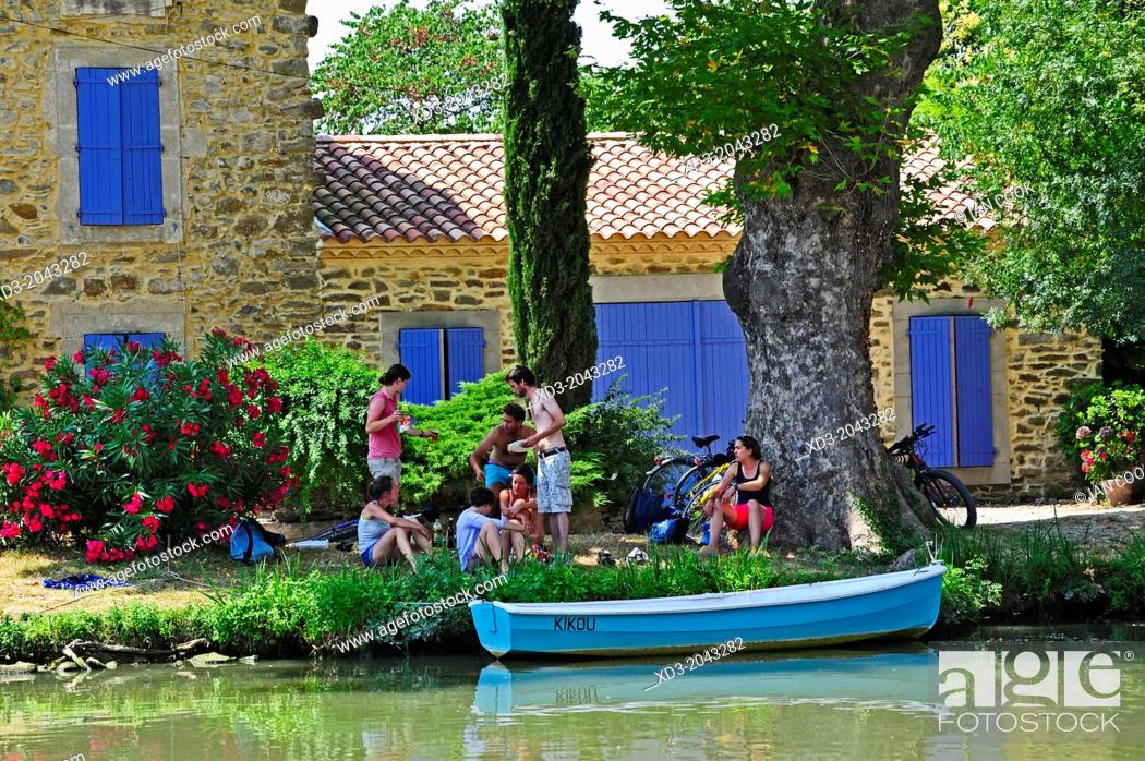Stock Photo: cyclists resting beside the Canal du Midi at Le Somail, Aude Department, France.