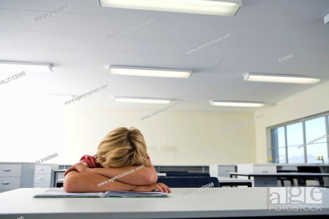 Stock Photo: School boy 10-13 in classroom, boy sleeping with head on his arms.