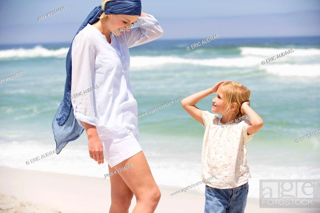Stock Photo: Woman with her daughter standing on the beach.