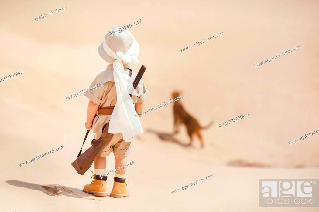 Stock Photo: Concept of travel and fascinating adventures. hild in suit of treasures seeker like Indiana Jones in the desert whit wild cat similar to tiger.