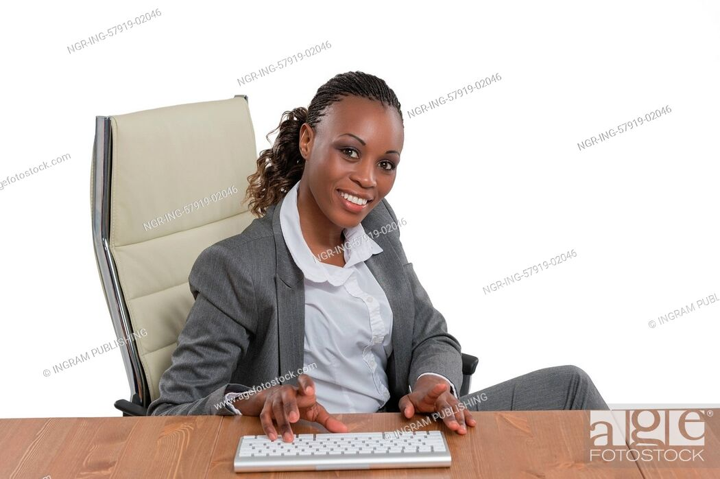 Stock Photo: African business woman sitting at her desk and working isolated on white background.