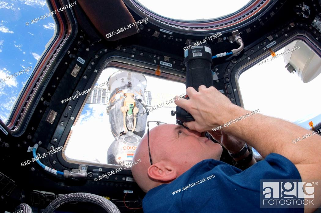 Stock Photo: NASA astronaut Scott Kelly, Expedition 25 flight engineer, uses a still camera to photograph the topography of a point on Earth from a window in the Cupola of.