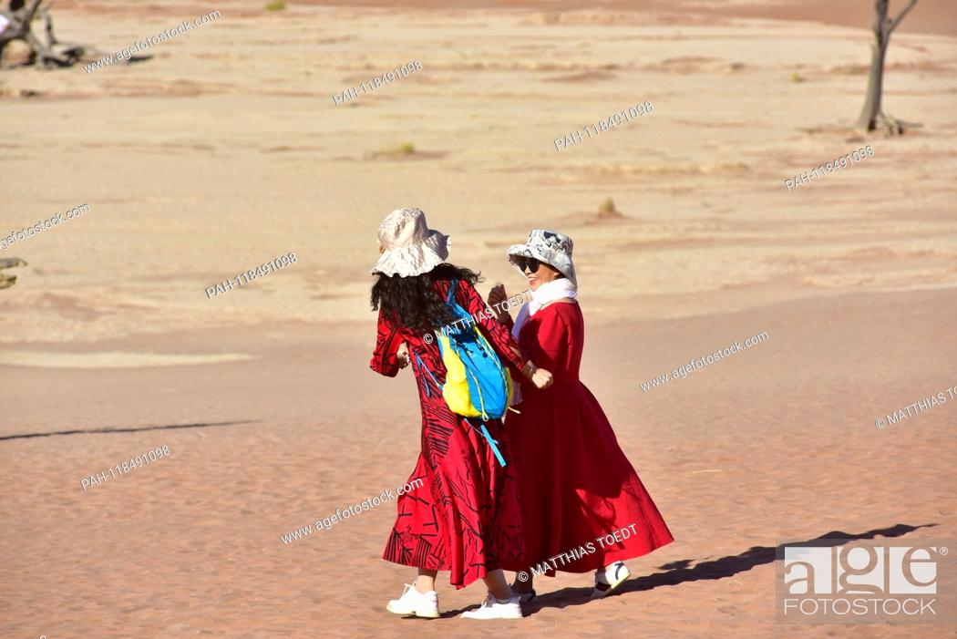 Stock Photo: Asian tourists in long, sun-protective clothes, in Dead Vlei, taken on 01.03.2019. The Dead Vlei is a dry, surrounded by tall dune clay pan with numerous dead.