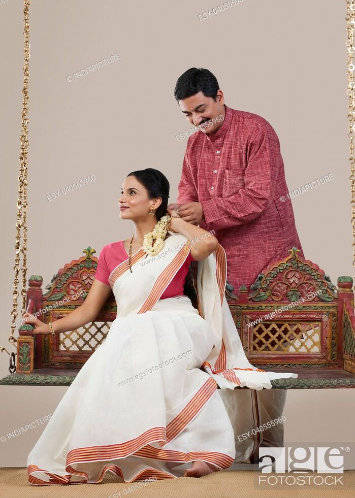 Stock Photo: South Indian man tying a Gajra on his wife's hair.