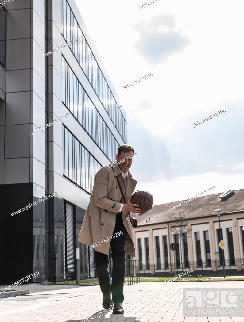 Photo de stock: Happy businessman playing basketball outside office building.