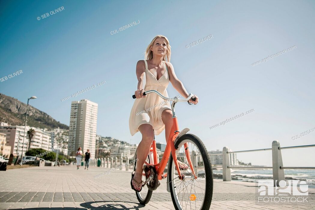 Stock Photo: Young woman cycling on seafront, Cape Town, South Africa.