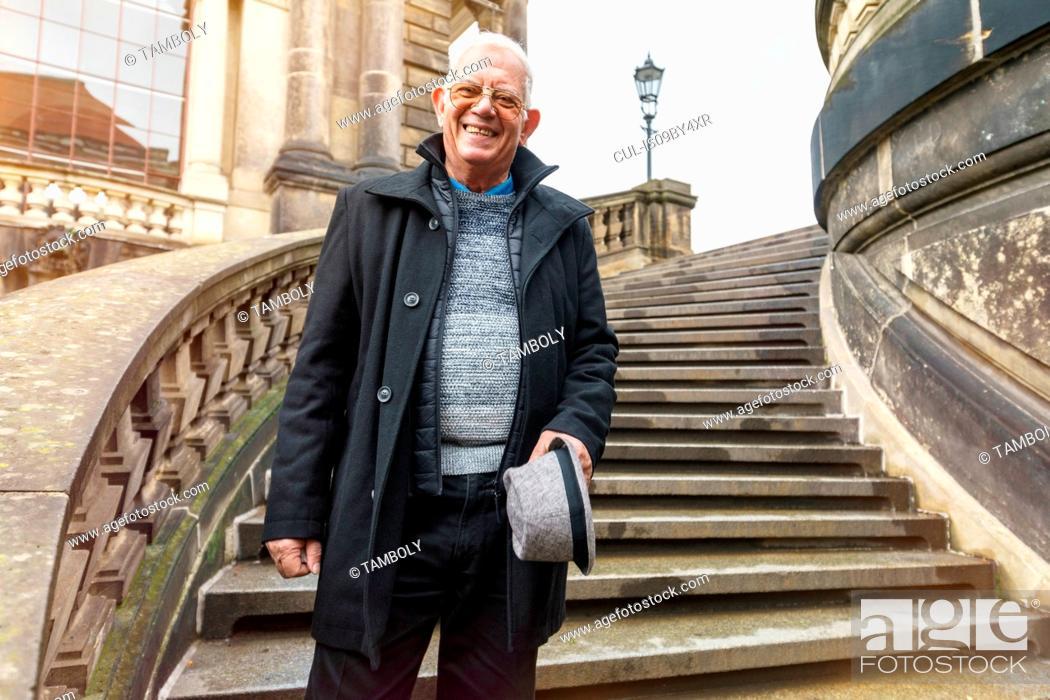 Stock Photo: Senior man exploring city standing on stairway, Dresden, Sachsen, Germany.
