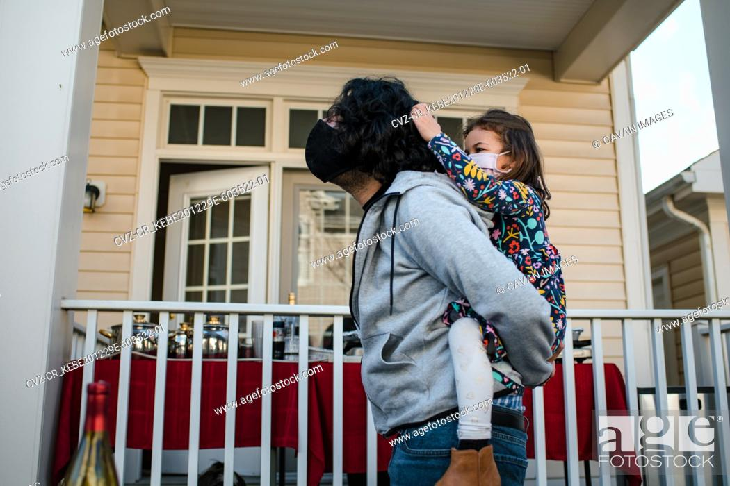 Stock Photo: Little girl pulling dad's hair during piggy back ride with masks.
