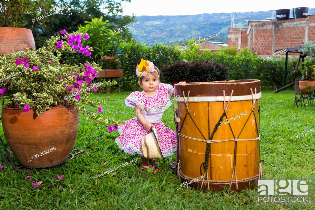 Imagen: little girl in traditional dance dress with flower bandana next to a drum.