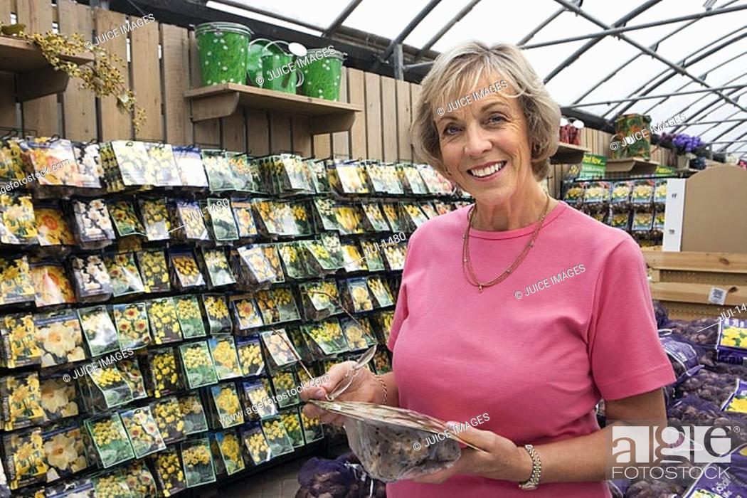 Stock Photo: Senior woman holding flower bulbs in garden centre, smiling, portrait.