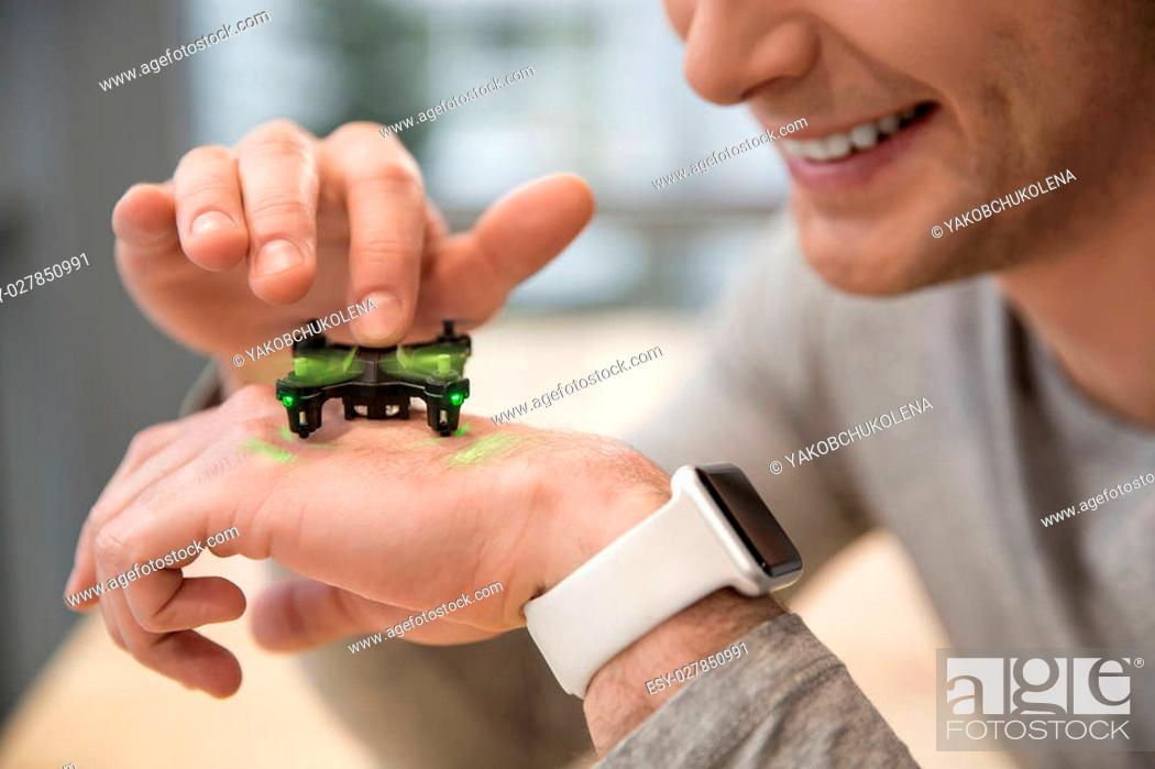 Stock Photo: Close up of arm of young man watching at the small quadrocopter in move. He is touching the moving propeller and smiling.