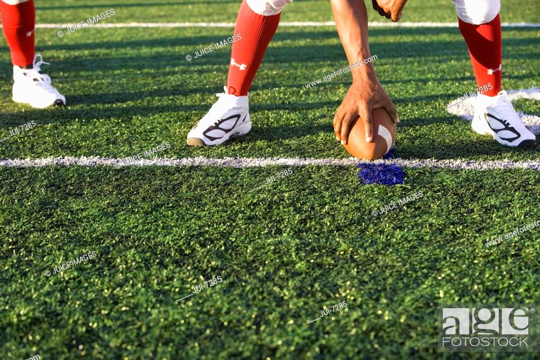 Stock Photo: American football running back, in red football strip, crouching with ball in scrimmage line during competitive game, front view, low-section.