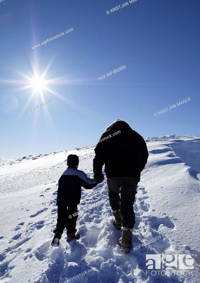 Stock Photo: Low angle view of a boy holding hand of his father and walking on a snow covered landscape.