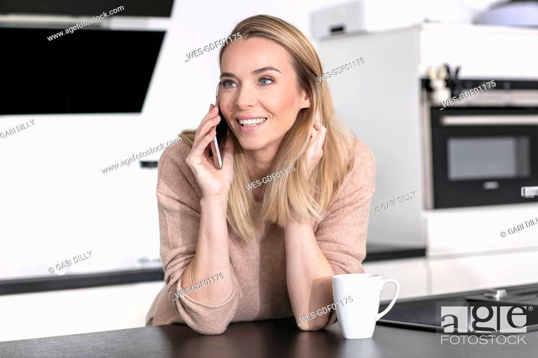 Stock Photo: Portrait of blond woman on the phone at home.