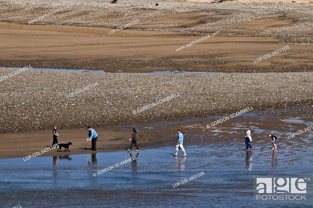 Stock Photo: Wales, Vale of Glamorgan, Ogmore. A family walking along the beach at Ogmore.