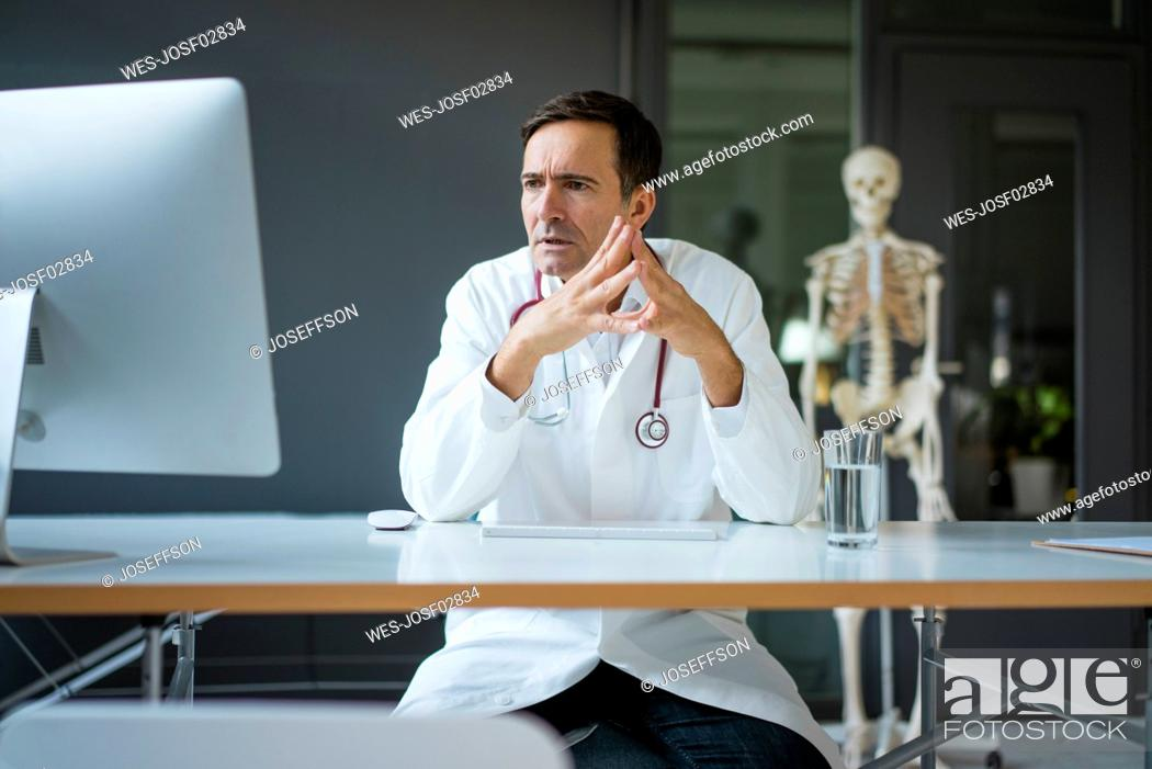 Stock Photo: Serious doctor sitting at desk in medical practice with skeleton in background.