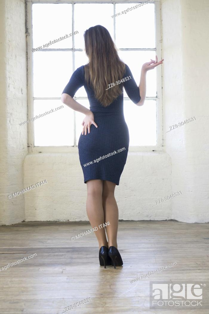 Stock Photo: Rear view of a woman standing by the window.