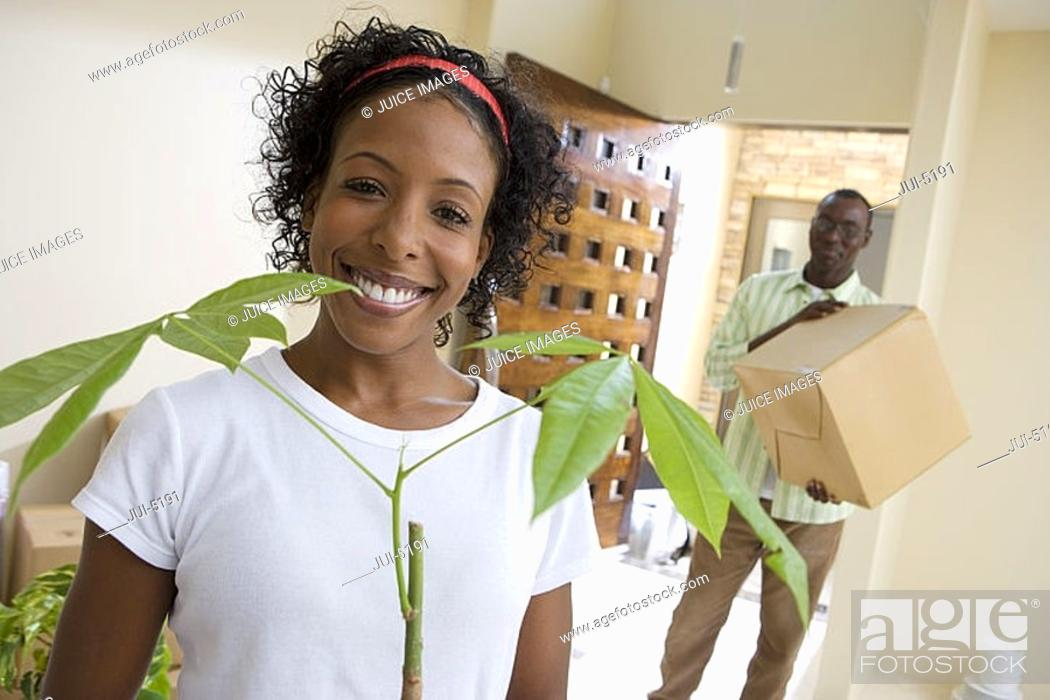 Stock Photo: Couple moving house, man carrying box in hallway, woman holding pot plant, smiling, portrait tilt.