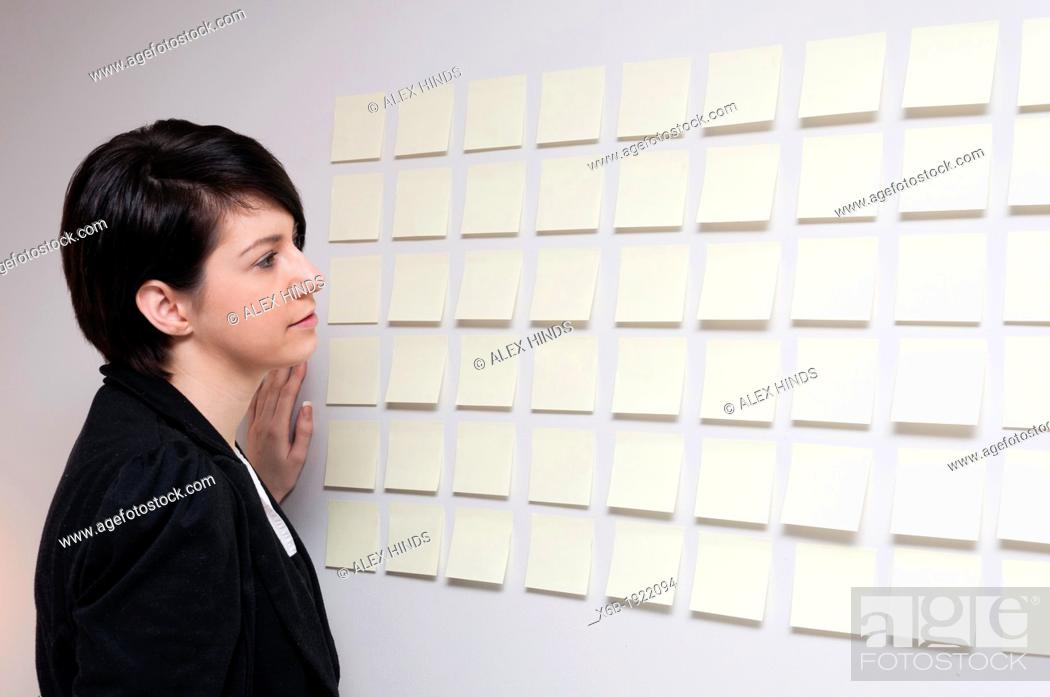 Stock Photo: Young woman next to wall of sticky paper notes.