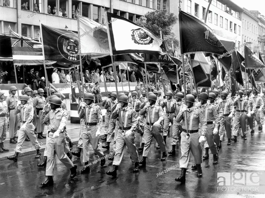 Stock Photo: A flag bearer troop of the US Army marching past a VIP stand during a parade on occasion of the American Independence Day on 4th July 1962 in Berlin.