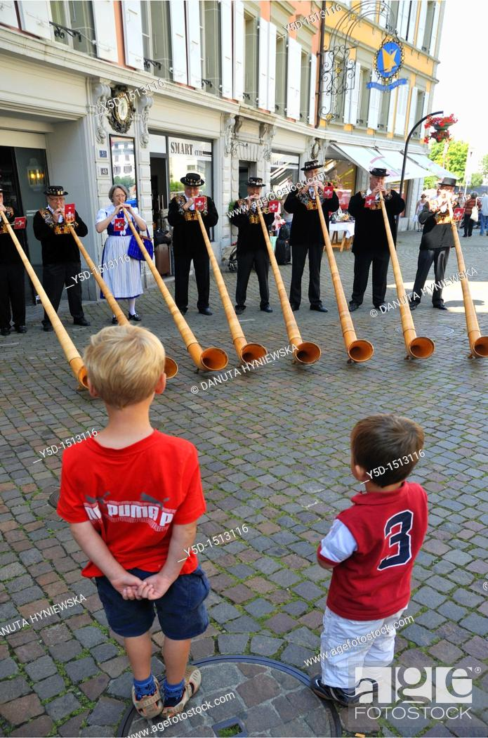 Stock Photo: two little boys watching group of players on traditional alpine horns, Vevey, Vaud, Switzerland.