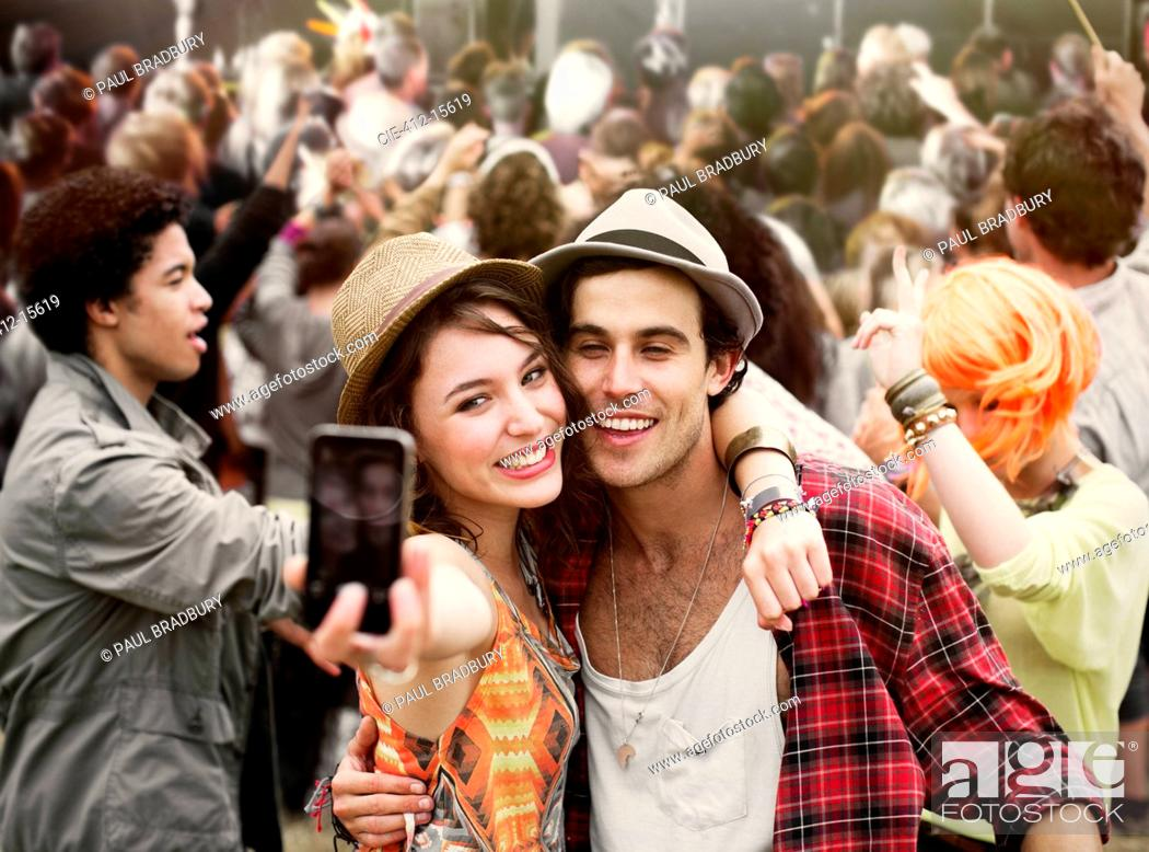 Stock Photo: Couple taking self-portrait at music festival.