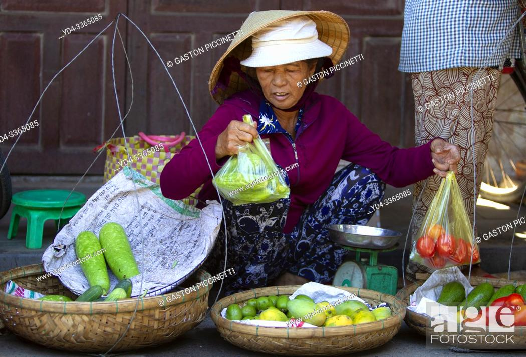 Imagen: Woman selling vegetables on the fresh food market of Hoi An Old Town, Vietnam, Southeast Asia.