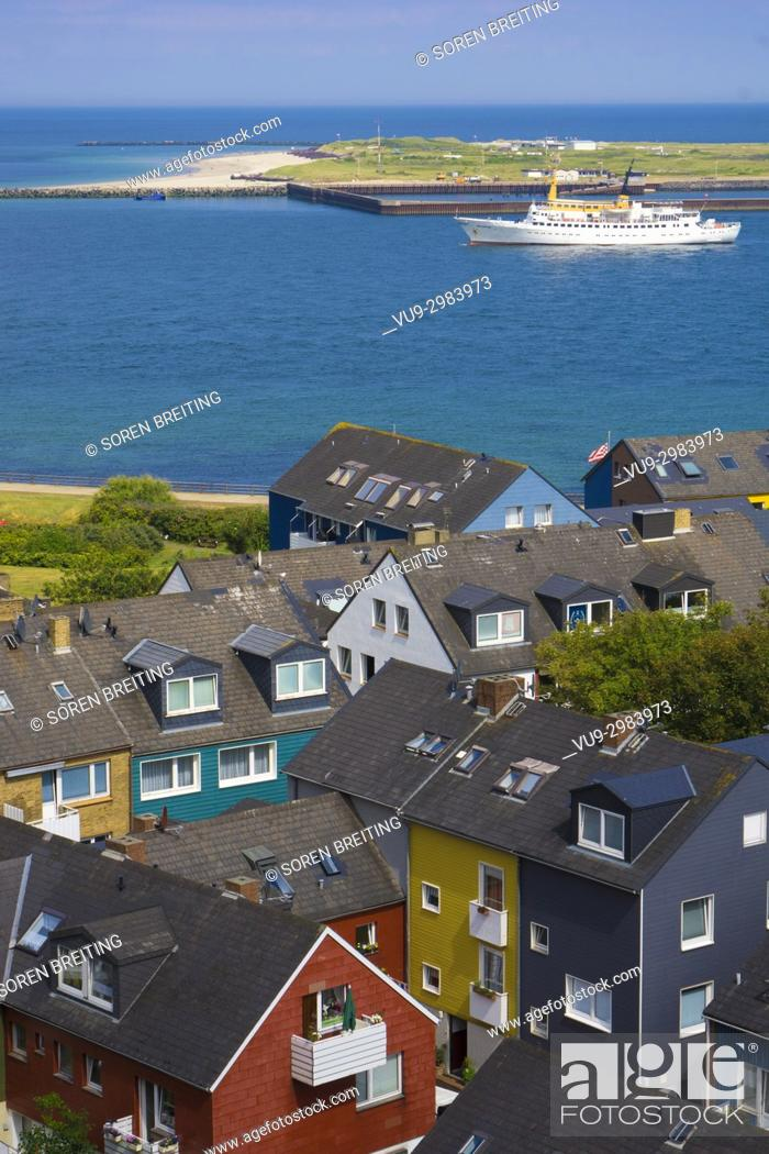 Stock Photo: Helgoland Germany colorful houses in town seen from the plateau of the main island toward the island Düne / Dune with ship.