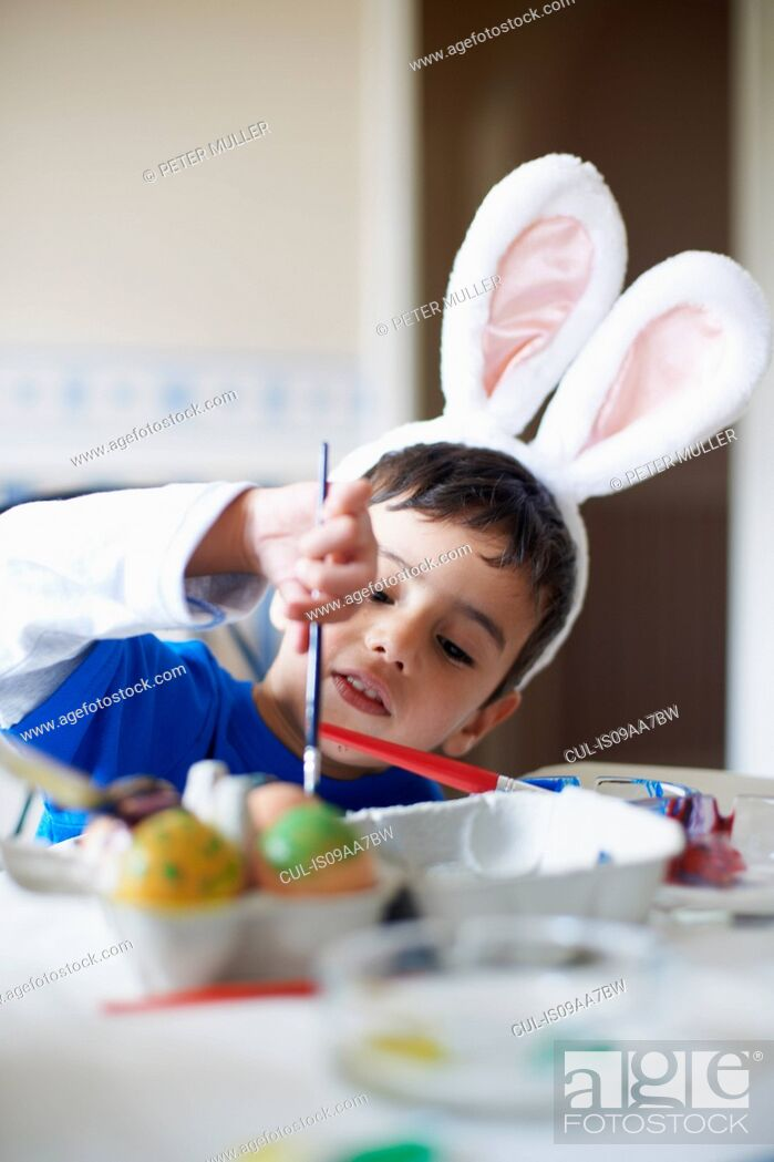 Stock Photo: Boy wearing bunny ears painting Easter eggs.