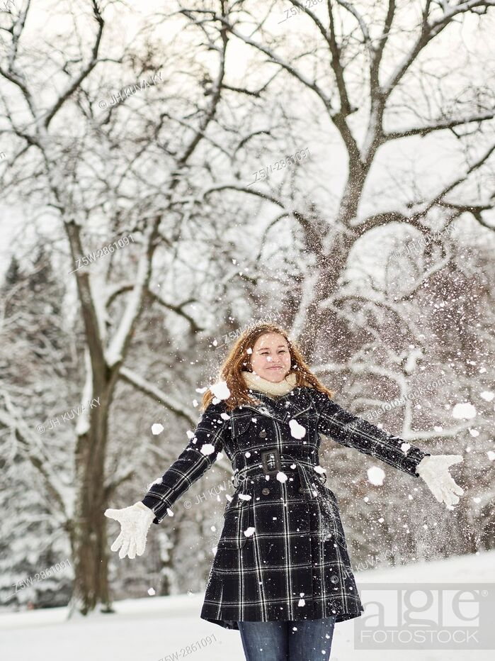 Stock Photo: Beautiful young girl wearing a winter coat and throwing snow up in the air, Finnish winter day on February.