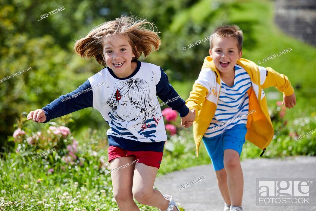 Imagen: Boy and girl running, holding hands, Getaria, Gipuzkoa, Basque Country, Spain.