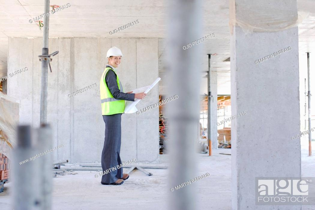 Stock Photo: Construction worker holding blueprint on construction site.