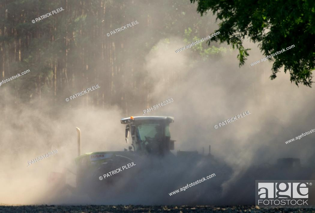 Stock Photo: A farmer stirs up dust as he ploughs a field near Biegen, Germany, 11 June 2015. Several regions of the German state Brandenburg have been suffering from a lack.
