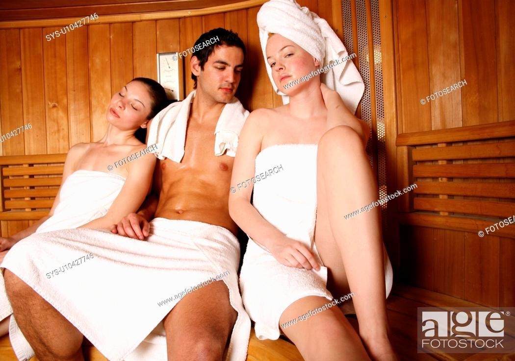 Stock Photo: Man with two young women enjoying a sauna.