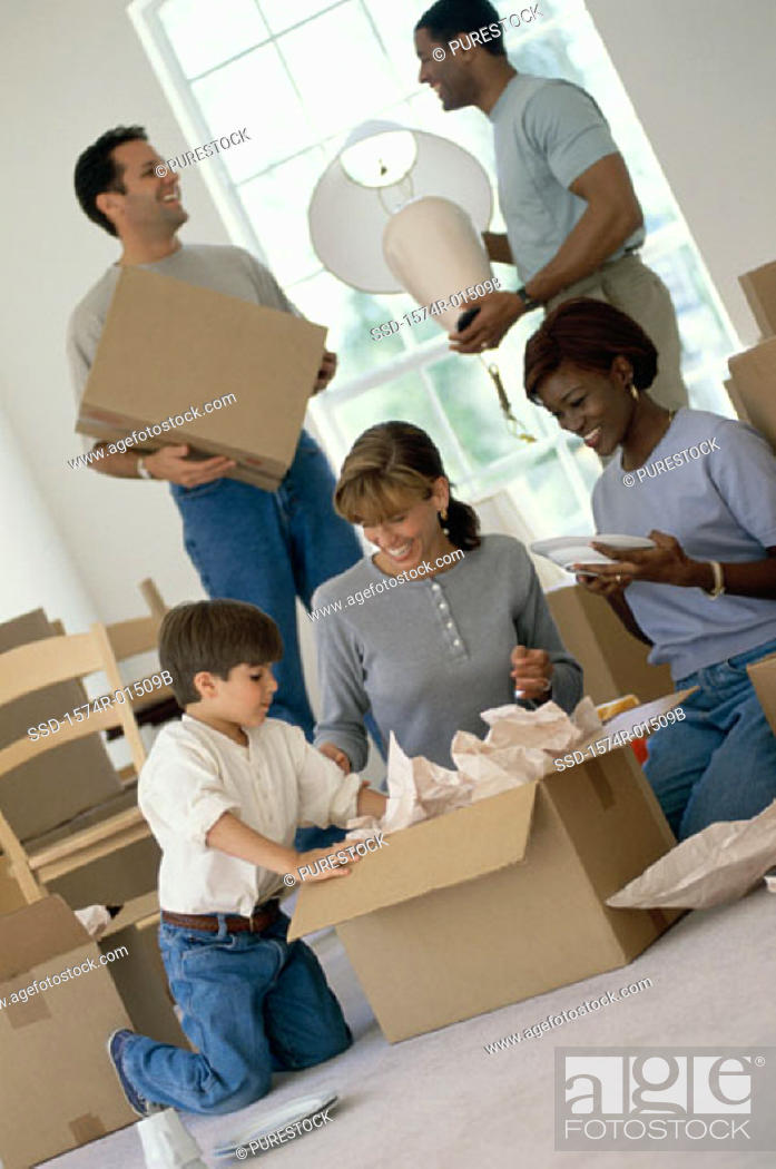 Stock Photo: Two young couples unpacking boxes in a new home.