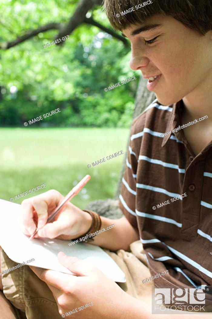 Stock Photo: Boy writing in a notebook.