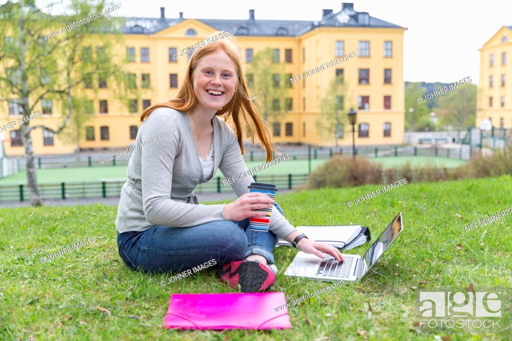 Stock Photo: Teenage girl on lawn using laptop.