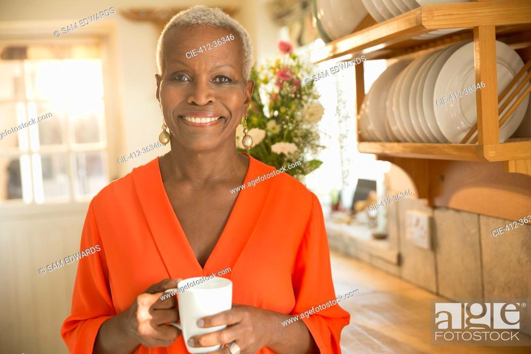 Stock Photo: Portrait smiling senior woman drinking coffee in kitchen.