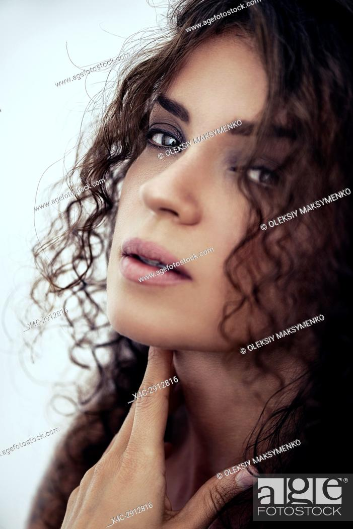 Stock Photo: Closeup sensual beauty studio portrait of a young caucasian woman with a deep expressive look on her face with long curly dark brown hair.
