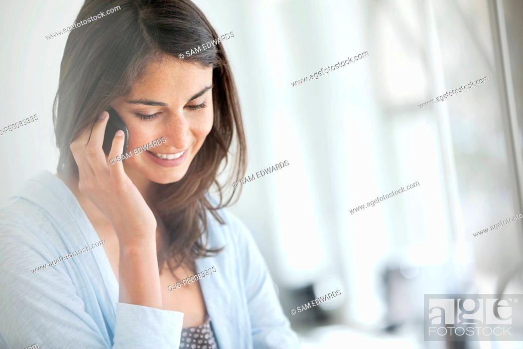 Stock Photo: Smiling woman talking on cell phone.