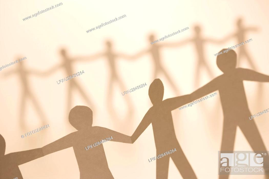 Stock Photo: Cutout paper men standing holding hands.