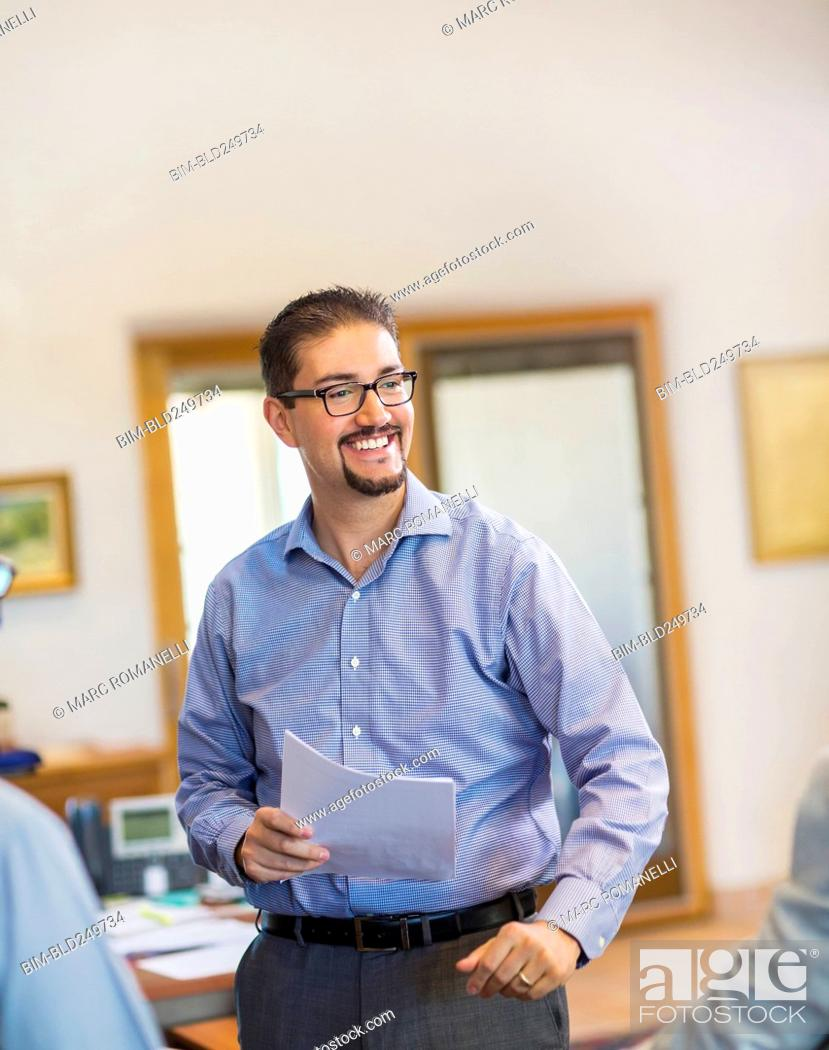 Stock Photo: Smiling Hispanic businessman holding paperwork in office.