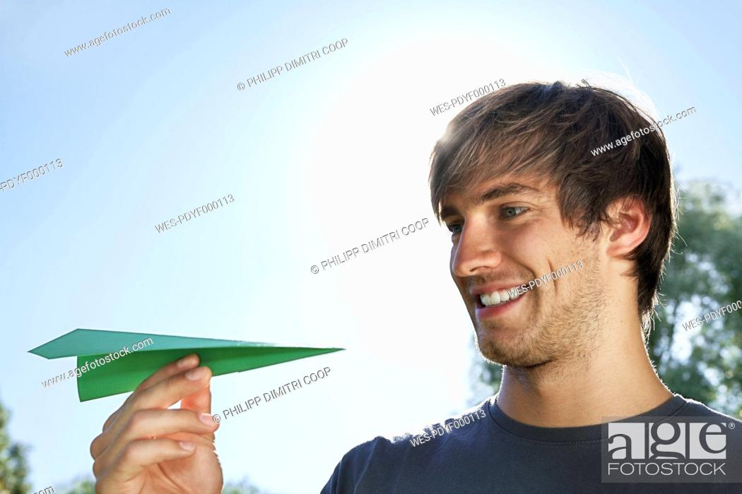 Stock Photo: Germany, Cologne, Young man holding paper plane.