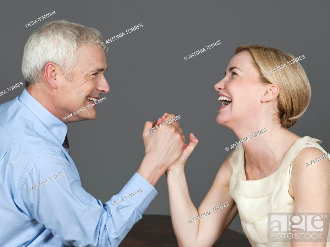 Stock Photo: Mature couple arm wrestling, smiling.