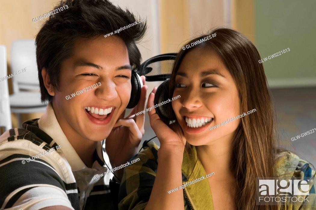 Stock Photo: Close-up of a young couple listening to music and smiling.