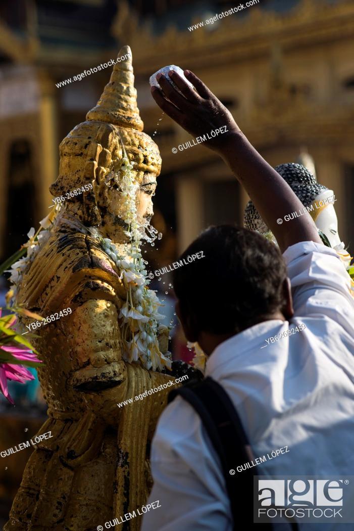 Stock Photo: People pouring water over a Buddha statue at the Shwedagon pagoda, Yangon, Myanmar.