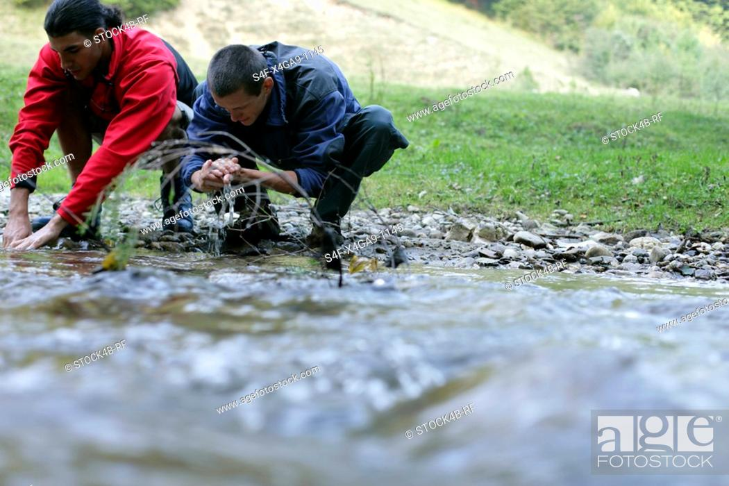 Stock Photo: Two young men washing themselves at the shore of a rivulet, selective focus.
