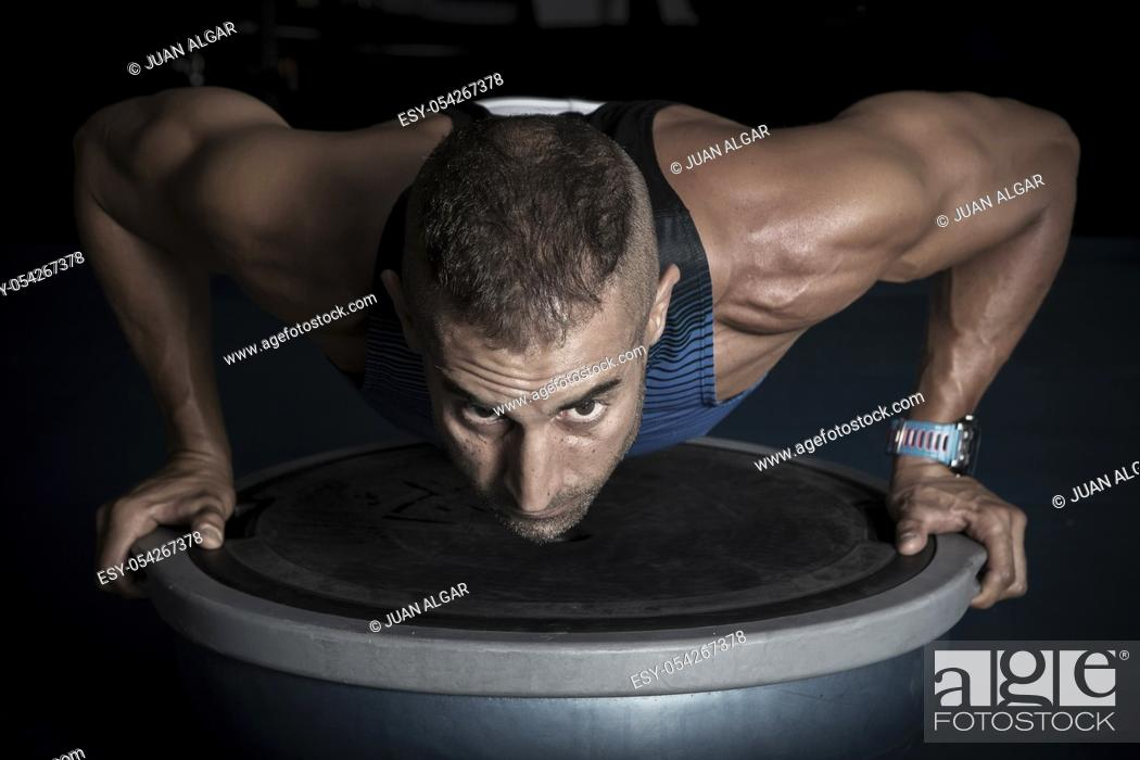 Stock Photo: Confident adult sportsman doing push-ups on bosu ball in gym looking forward.